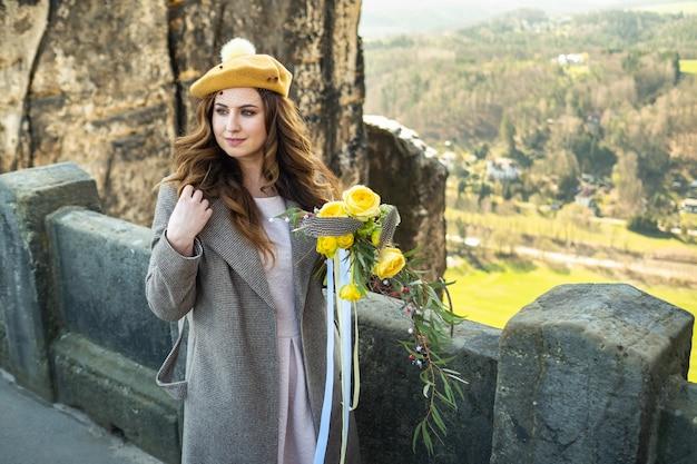Een meisje in een grijze jas en hoed met een boeket bloemen