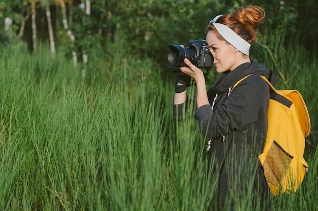 Een meisje in een grijze jas met een gele rugzak heeft een professionele foto-videocamera in haar handen. tegen de achtergrond van groene natuur en bos.