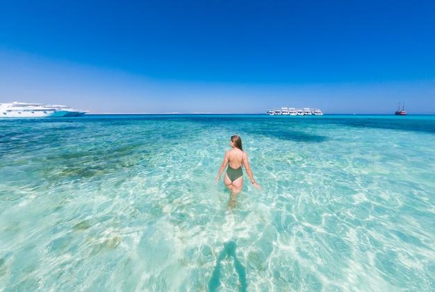 Een meisje in een groen zwempak om te baden in het blauwe water van de rode zee. het is zonnig buiten