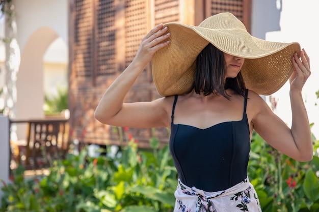 Een meisje in een grote strooien hoed in de buurt van de gevel van een oud huis op een hete zomerdag.