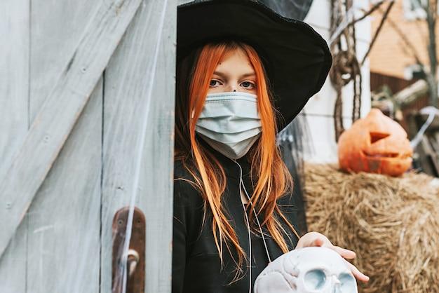 Een meisje in een heksenkostuum dat een beschermend gezichtsmasker draagt op een halloween-feest in een nieuwe realiteit vanwege de covid-pandemie