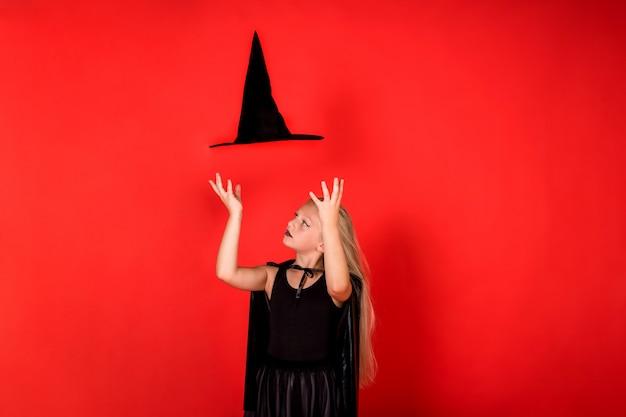 Een meisje in een heksenkostuum doet een truc met een vliegende hoed op een rode geïsoleerde muur met ruimte voor tekst
