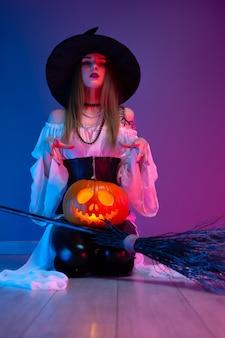 Een meisje in een heksenkostuum voor halloween met een bezem en een pompoen in neonlicht
