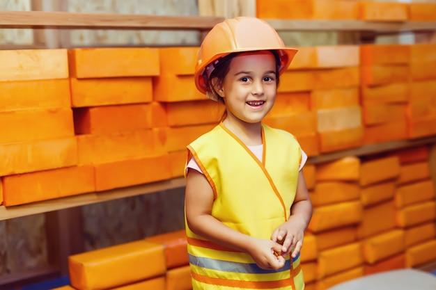 Een meisje in een helm op de bouwplaats van een houten frame huis