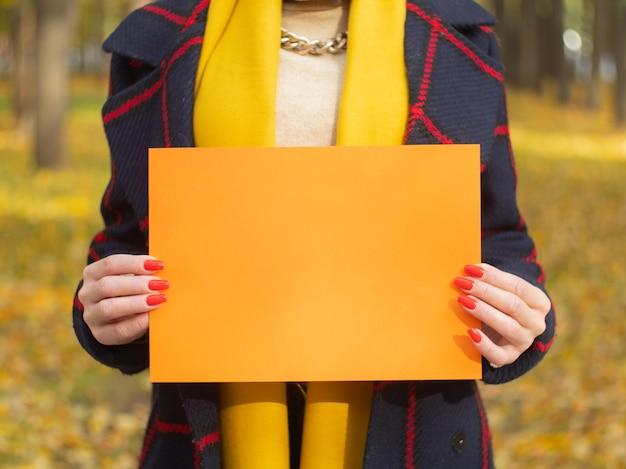 Een meisje in een herfstpark houdt een stuk papier vast voor je tekst. reclame boekje