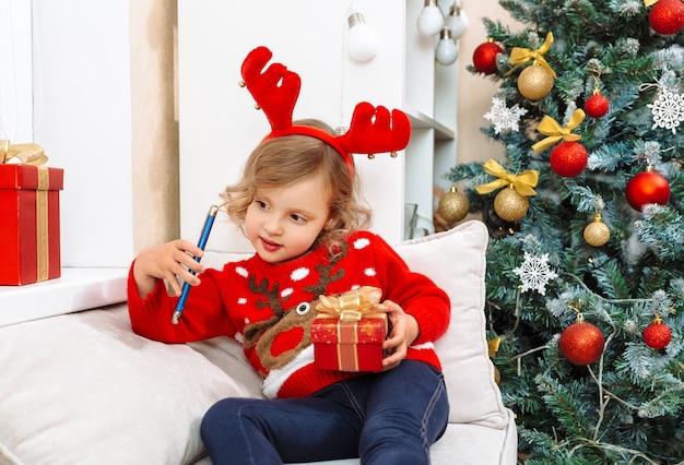 Een meisje in een hertenkostuum communiceert met zijn familieleden aan de telefoon en bedankt hen voor geschenken