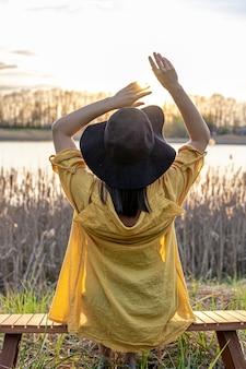 Een meisje in een hoed en in casual stijl zit op een bankje bij het meer bij zonsondergang