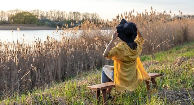Een meisje in een hoed en in casual stijl zit op een bankje in de buurt van het meer bij zonsondergang.