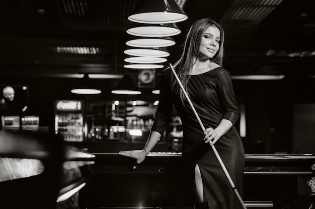 Een meisje in een hoed in een biljartclub met een keu in haar handen. biljartspel. zwart-witfoto.