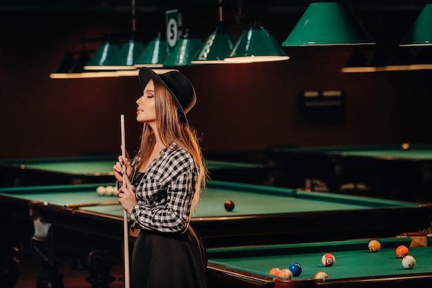 Een meisje in een hoed in een biljartclub met een keu in haar handen. poolspel.