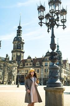 Een meisje in een jas en hoed in een straat in de stad dresden