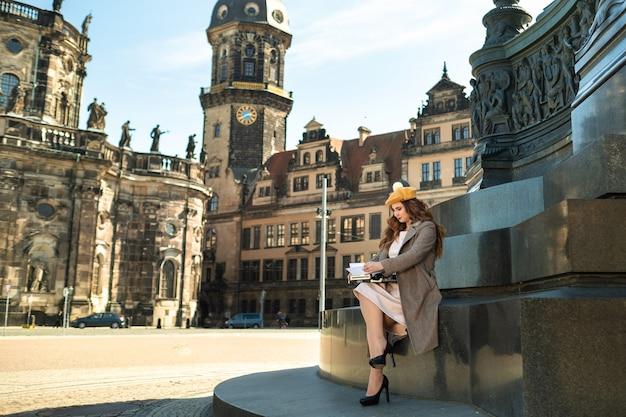 Een meisje in een jas en hoed zit in het centrum van de oude stad van dresden en typt op een typemachine. duitsland.