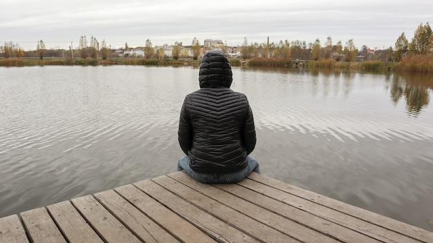 Een meisje in een jas zit bij koud herfstweer op een houten brug bij het meer. dipresia of alleen dromen. eén op één denken met de natuur.