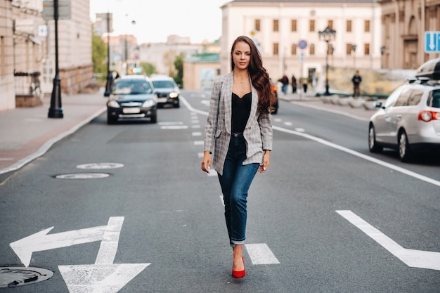 Een meisje in een jasje en lang haar loopt door de oude stad. een mooi meisje glimlacht. meisje op de weg.