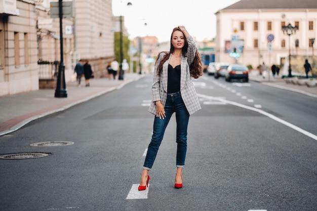 Een meisje in een jasje en lang haar loopt door de oude stad.