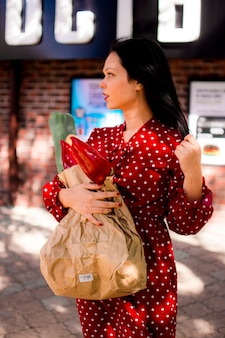 Een meisje in een jurk loopt over straat met een papieren zak met boodschappen in haar handen.