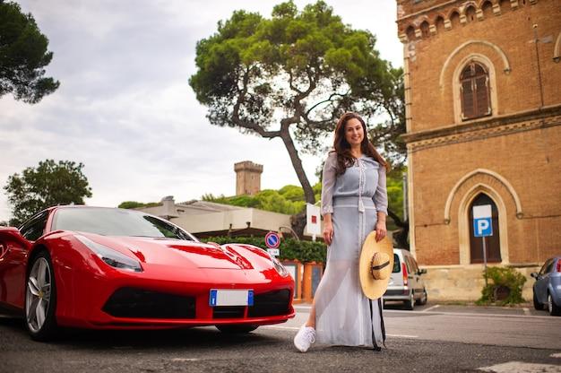 Een meisje in een jurk naast een sportwagen in een stadsstraat in toscane, italië.