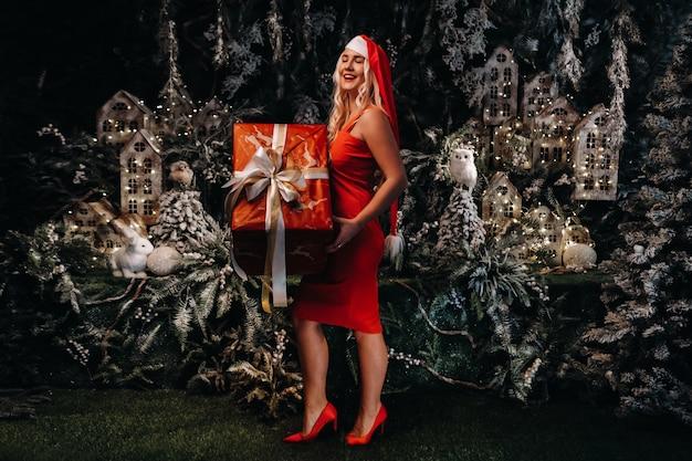 Een meisje in een kerstmuts met een groot kerstcadeau in haar handen op een fantastische kerstachtergrond. een lachende vrouw in een rode jurk op de achtergrond van kerstbomen en kleine huizen