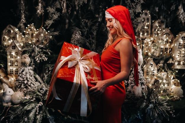 Een meisje in een kerstmuts met een groot kerstcadeau in haar handen