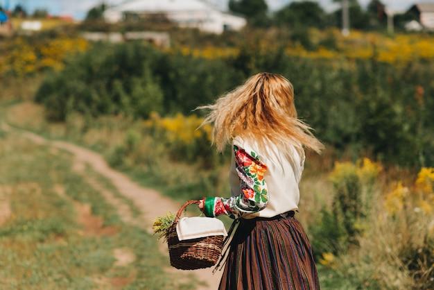 Een meisje in een klederdracht en met een mand met bloemen loopt op een groen veld klederdracht