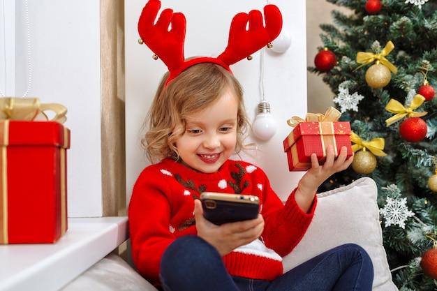 Een meisje in een klein hertenkostuum communiceert met familieleden aan de telefoon en bedankt hen voor geschenken
