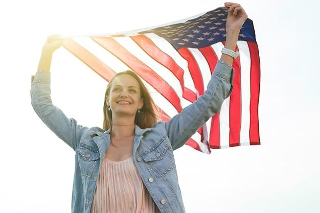 Een meisje in een koraaljurk en een spijkerjasje houdt de vlag van de verenigde staten in haar handen. 4 juli independence day.
