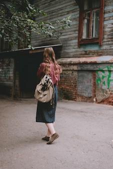 Een meisje in een lange rok met een rugzak loopt door het achteraanzicht van de stad.