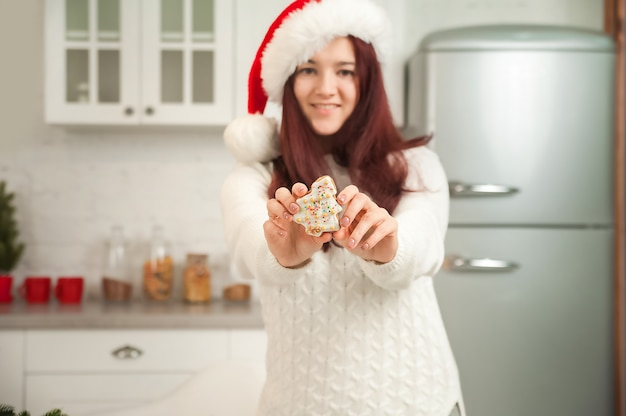Een meisje in een lichte scandinavische keuken bereidt kerstdiner en lunch jonge vrouw en peperkoek close-up en kopieer de ruimte