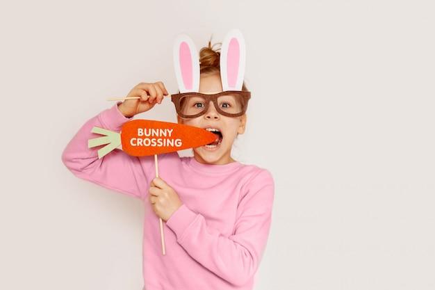Een meisje in een maskerbril met konijnenoren houdt een wortel vast met de inscriptie bunny crossing