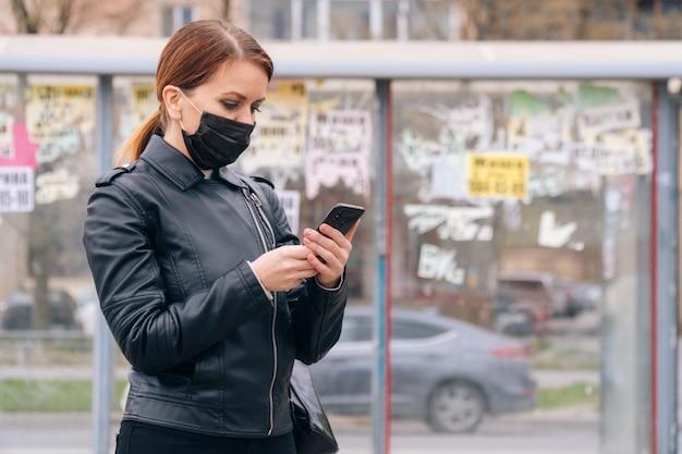 Een meisje in een medisch masker staat alleen bij een halte die op vervoer wacht. het concept van sociale afstand en veiligheid tijdens een pandemie
