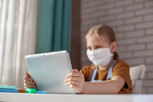 Een meisje in een medisch masker studeert thuis met een digitale tabletlaptop en doet huiswerk. afstandsonderwijs online onderwijs