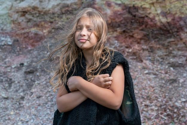 Een meisje in een mouwloos vest van dierenhuid schrikt terug voor het feit dat ze het koud heeft