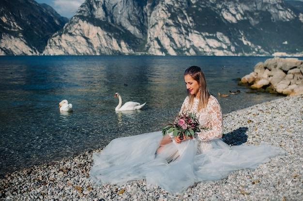 Een meisje in een nette witte jurk zit aan de oever van het gardameer, een vrouw wordt gefotografeerd tegen de achtergrond van een berg en een meer in italië, torbole.