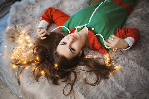 Een meisje in een nieuwjaarsoverall met een feestelijke stemming ligt op een bed rond lichtgevende slingers