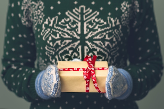 Een meisje in een nieuwjaarstrui heeft een cadeautje. cadeaus voor mannen. vrolijk kerstfeest. cadeau voor een meisje. sweater met kerstornament. gebreide jurk.