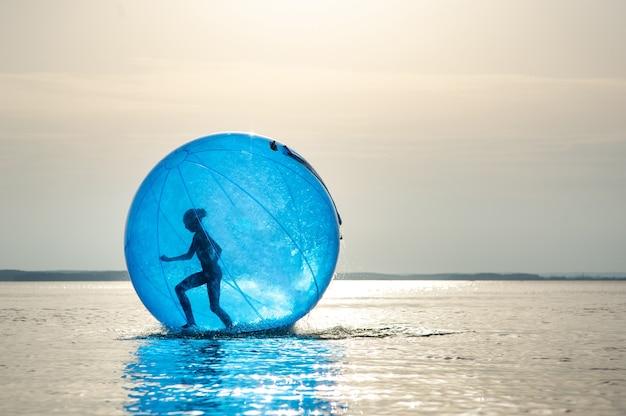 Een meisje in een opblaasbare attractie in de vorm van een bal op zee.