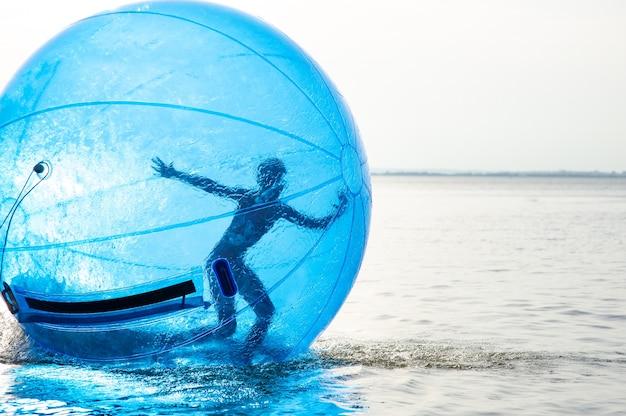 Een meisje in een opblaasbare attractie in de vorm van een bal op zee