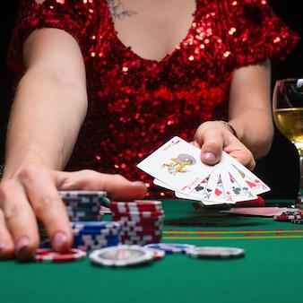 Een meisje in een rode avondjurk speelt poker in een nachtcasino
