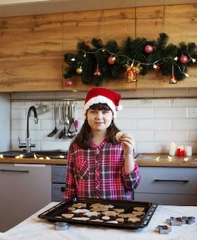Een meisje in een rode hoed en een rood geruit overhemd staat in de keuken naast een dienblad met koekjes