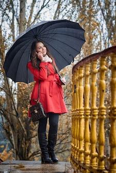 Een meisje in een rode jas onder een zwarte paraplu praat aan de telefoon