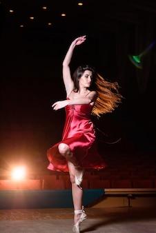 Een meisje in een rode jurk danst op het podium.