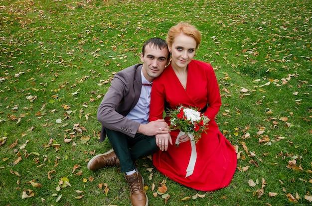 Een meisje in een rode jurk en een man in een pak zitten op het gras. jonggehuwden op het gazongras