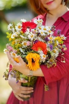Een meisje in een rode jurk houdt een prachtig bloemboeket in haar handen