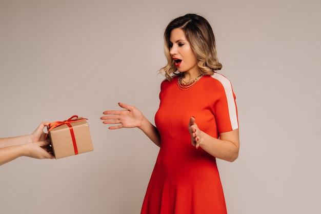 Een meisje in een rode jurk krijgt een geschenk in haar handen