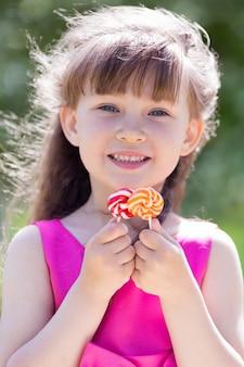 Een meisje in een rode jurk met snoepjes in haar handen.