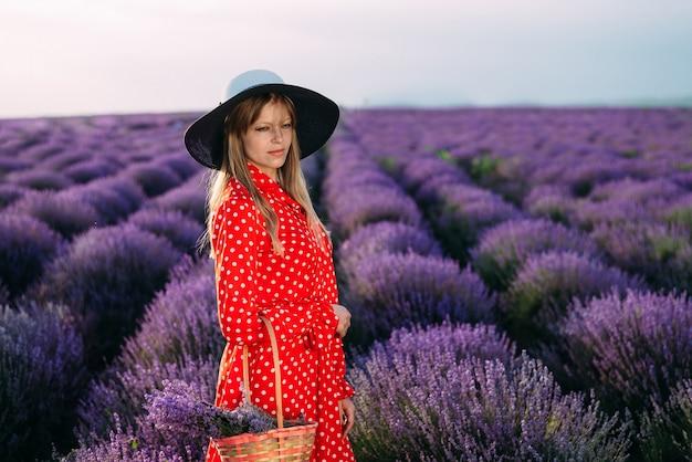 Een meisje in een rode jurk staat midden in een lavendelveld met een mand met bloemen bij de hand.