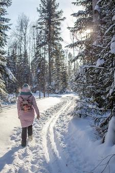 Een meisje in een rood jasje loopt op een winterse dag door een besneeuwd bos. achteraanzicht.