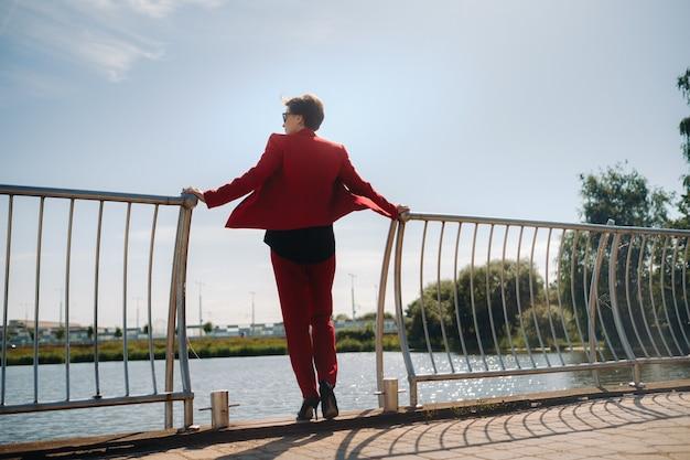 Een meisje in een rood pak staat op een pier bij het meer