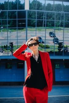 Een meisje in een rood pak staat tegen de achtergrond van een modern gebouw in de stad