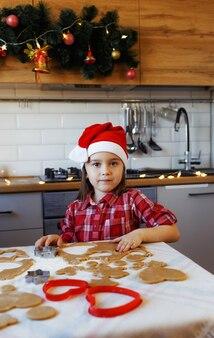 Een meisje in een rood shirt en een kerstmuts bereidt gemberkoekjes voor op de feestelijke kersttafel in de keuken.